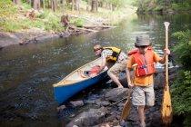 Père et fils en poussant le canot — Photo de stock