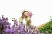 Woman gathering flowers in garden — Stock Photo