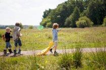 Trois enfants marchant sur le chemin de terre — Photo de stock