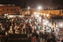 Crowds of shoppers and market stalls at night — Stock Photo