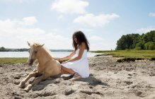 Girl petting horse on sandy beach — Stock Photo