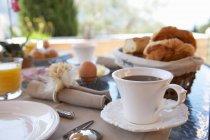 Café e comida na mesa de café da manhã — Fotografia de Stock
