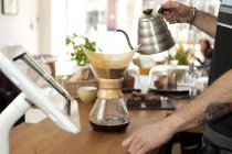 Mains de café garçon verser l'eau bouillante dans le pot de café filtre — Photo de stock