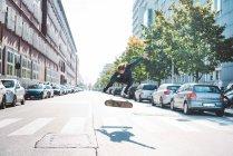 Joven skateboarder urbano masculino saltando en el aire en el cruce peatonal - foto de stock
