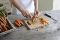 Mãos de adolescente descascar cenouras — Fotografia de Stock