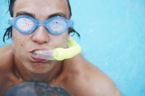 Portrait of young man wearing scuba goggles in swimming pool — Stock Photo