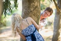 Couple playing around tree trunk — Stock Photo