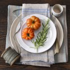 Tomatoes with rosemary on plates — Stock Photo