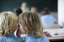 Susurrando a los escolares en el aula - foto de stock