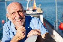 Retrato de pescador sonriente en barco de pesca - foto de stock