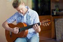 Mann spielt Gitarre im Wohnzimmer — Stockfoto