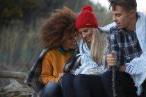 Tre amici adulti seduti rannicchiati insieme sulla spiaggia al tramonto — Foto stock