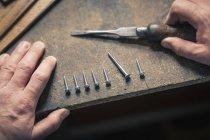 Vista superior de las manos sosteniendo cincel, tornillos en fila - foto de stock