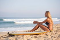Жінка сидить з дошки для серфінгу на пляжі — стокове фото