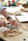 Man slicing chicken — Stock Photo