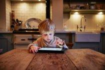 Niño usando tableta en la mesa - foto de stock