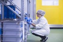 Ouvrier d'usine accroupi dans la salle de stockage recherche conteneurs de stockage — Photo de stock
