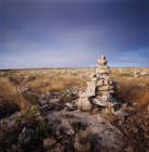 Pyramid of stones in rocky field — Stock Photo