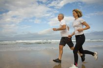 Couple running on a beach — Stock Photo