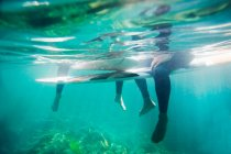 Couple's legs and surfboards underwater — Stock Photo