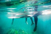 Paar Beine und Surfbretter unter Wasser — Stockfoto
