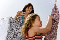 Ragazza con madre appeso vestiti — Foto stock