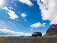 Jeep parked on gravel in rural landscape — Stock Photo