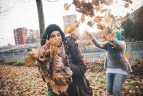 Zwei junge Frauen Freunde spielen kämpfen mit Herbstlaub im park — Stockfoto