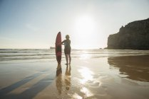 Silhouetted senior woman standing on beach with surfboard, Camaret-sur-mer, Brittany, France — Stock Photo
