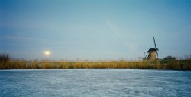 Ländliche Windmühle auf zugefrorenen Fluss bei Nacht — Stockfoto