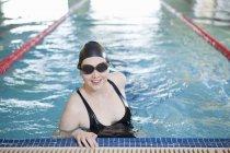 Женщина улыбается в закрытом бассейне — стоковое фото