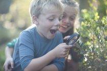 Брат и сестра обнаруживают растения с лупой в саду — стоковое фото