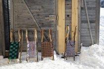 Rangée de quatre traîneaux appuyé contre la cabane en rondins — Photo de stock