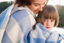 Madre e figlia avvolte in una coperta — Foto stock