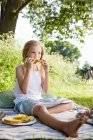 Sitting girl eating pineapple — Stock Photo