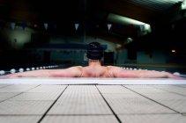 Спортивный мужчина опираясь на бассейн — стоковое фото