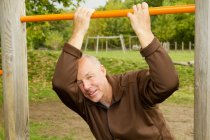 Older man hanging from jungle gym — Stock Photo