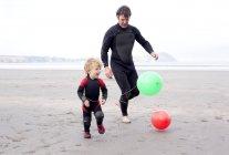 Батько і син, граючи з повітряних куль на пляжі — стокове фото
