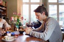 Людина за допомогою стільникового телефону за обіднім столом — стокове фото