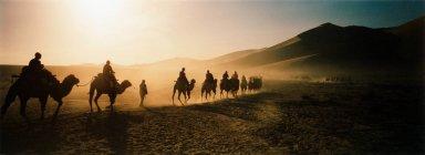 Touristen auf Kamelkarawane ziehen durch Dünen — Stockfoto