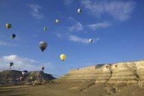 Повітряні кулі плаває в відстань по горах — стокове фото