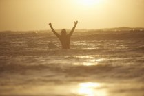 Silhouette of young male surfer with arms raised at sea, Devon, England, UK — Stock Photo