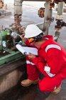 Travailleur notant jauge à la raffinerie de pétrole — Photo de stock