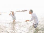 Casal brincando em ondas na praia — Fotografia de Stock