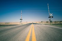 Railroad crossing in desert — Stock Photo