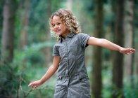 Giovane ragazza braccia disteso bosco — Foto stock