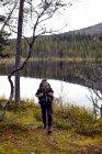 Туристы, проходя мимо озера, Kesankijarvi, Лапландии, Финляндия — стоковое фото