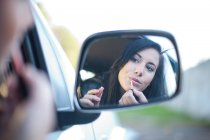 Young woman applying lipstick in car mirror — Stock Photo