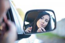 Mujer joven aplicar lápiz labial en el espejo de coche - foto de stock