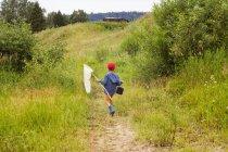 Niño caminando por el campo, llevando red de pesca, vista trasera - foto de stock